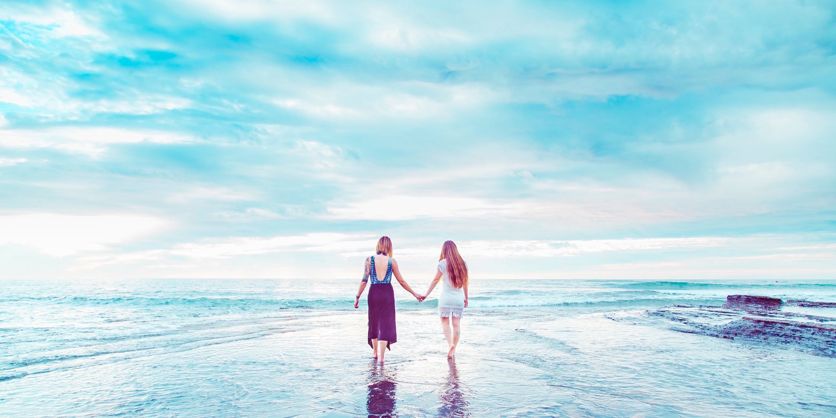 Two people holding hands walking in shallow ocean water underneath expansive blue sky