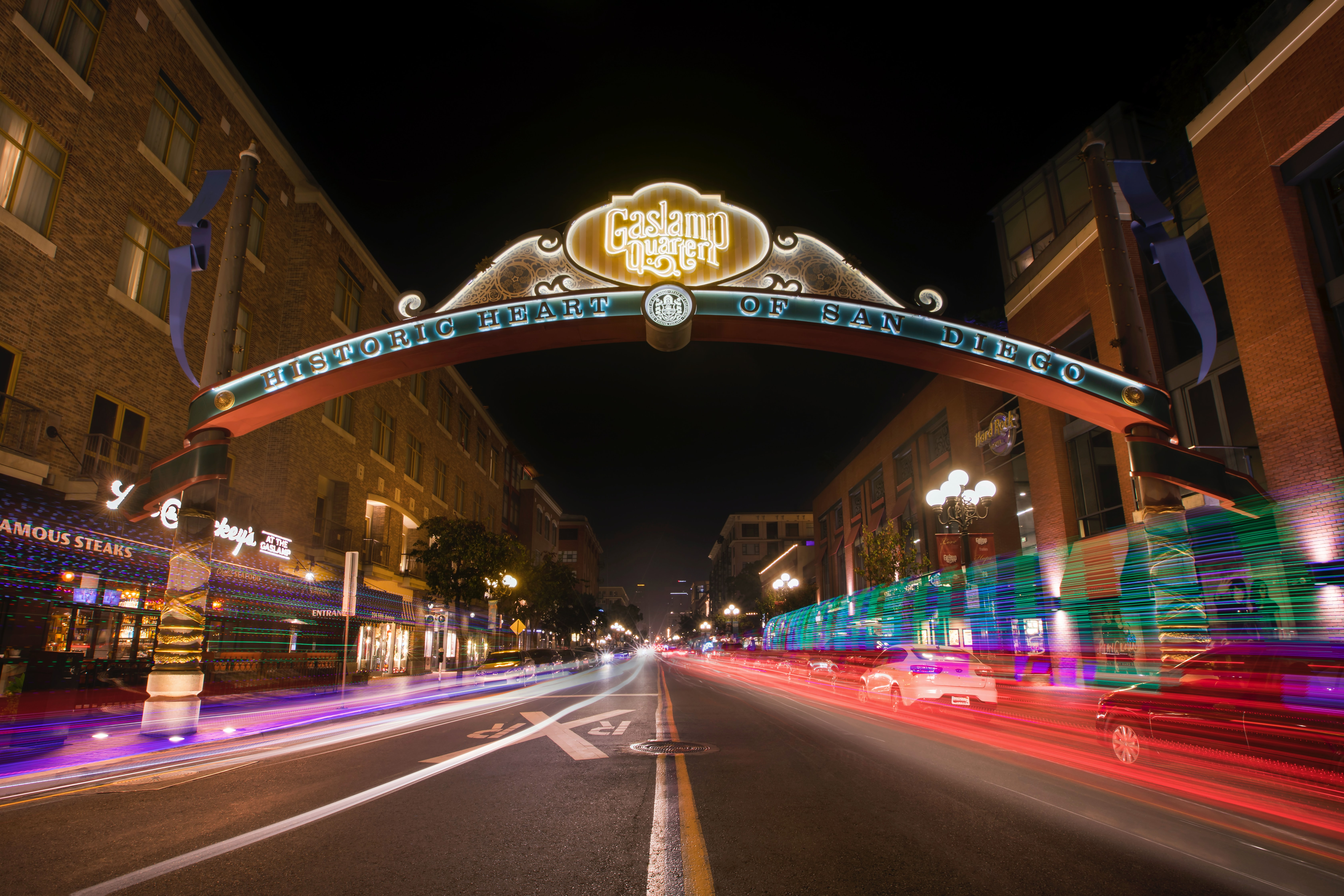 Photograph of San Diego's Gaslamp sign at night with motion blurred lights underneath
